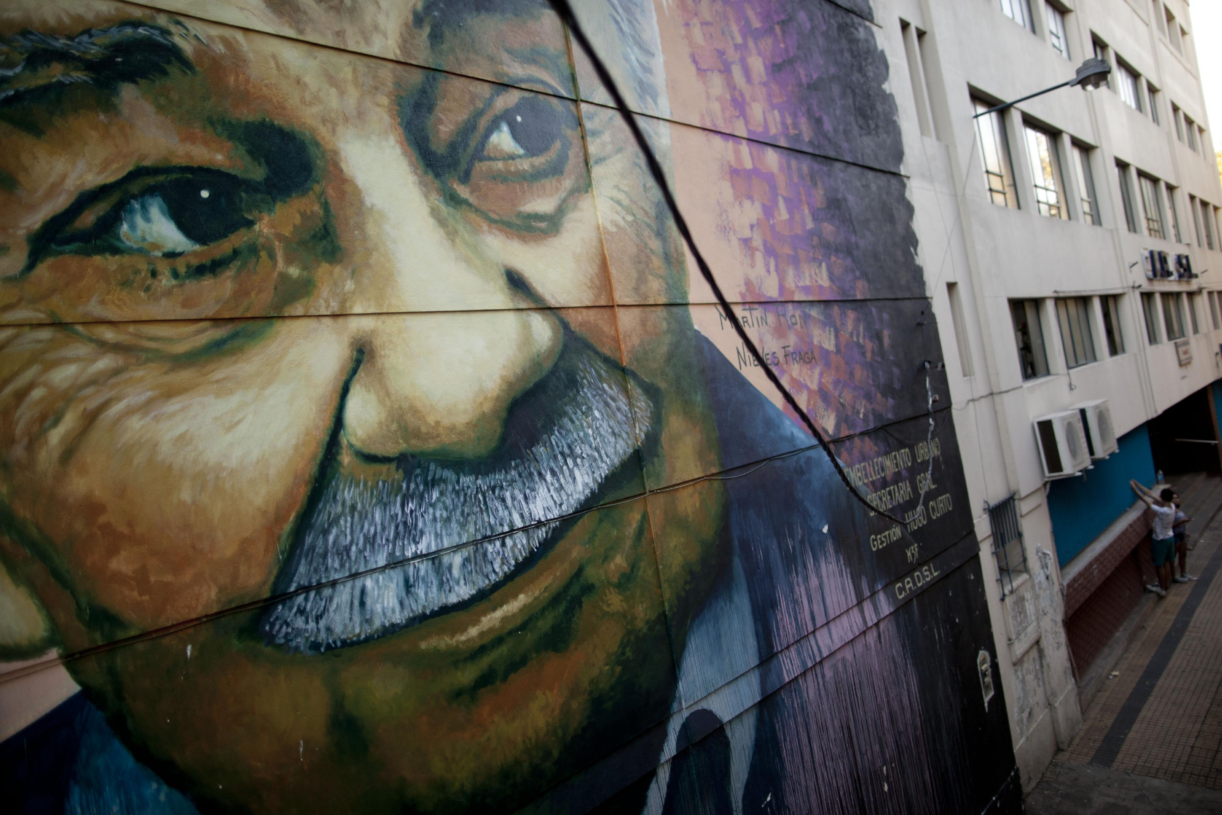 In this March 28, 2013 photo, a mural depicting Argentine writer Ernesto Sabato, created by artist Martin Ron, covers a building there Sabato once lived in Buenos Aires, Argentina. Local painters, including Argentine Martin Ron, take advantage of the relatively lax rules for street art, and they consider local vehicular and pedestrian traffic patterns before painting to get the best exposure for their work. (AP Photo/Natacha Pisarenko)