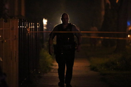 Police investigate the scene where a 7-year-old boy was killed and a 26-year-old woman was injured in a shooting in Chicago, July 2015.