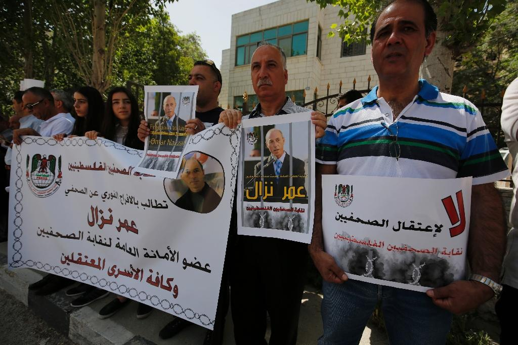 Palestinian journalists hold placards and banners during a demonstration on April 24, 2016 outside the Red Cross offices in the West Bank city of Ramallah in support of their detained colleague Omar Nazza