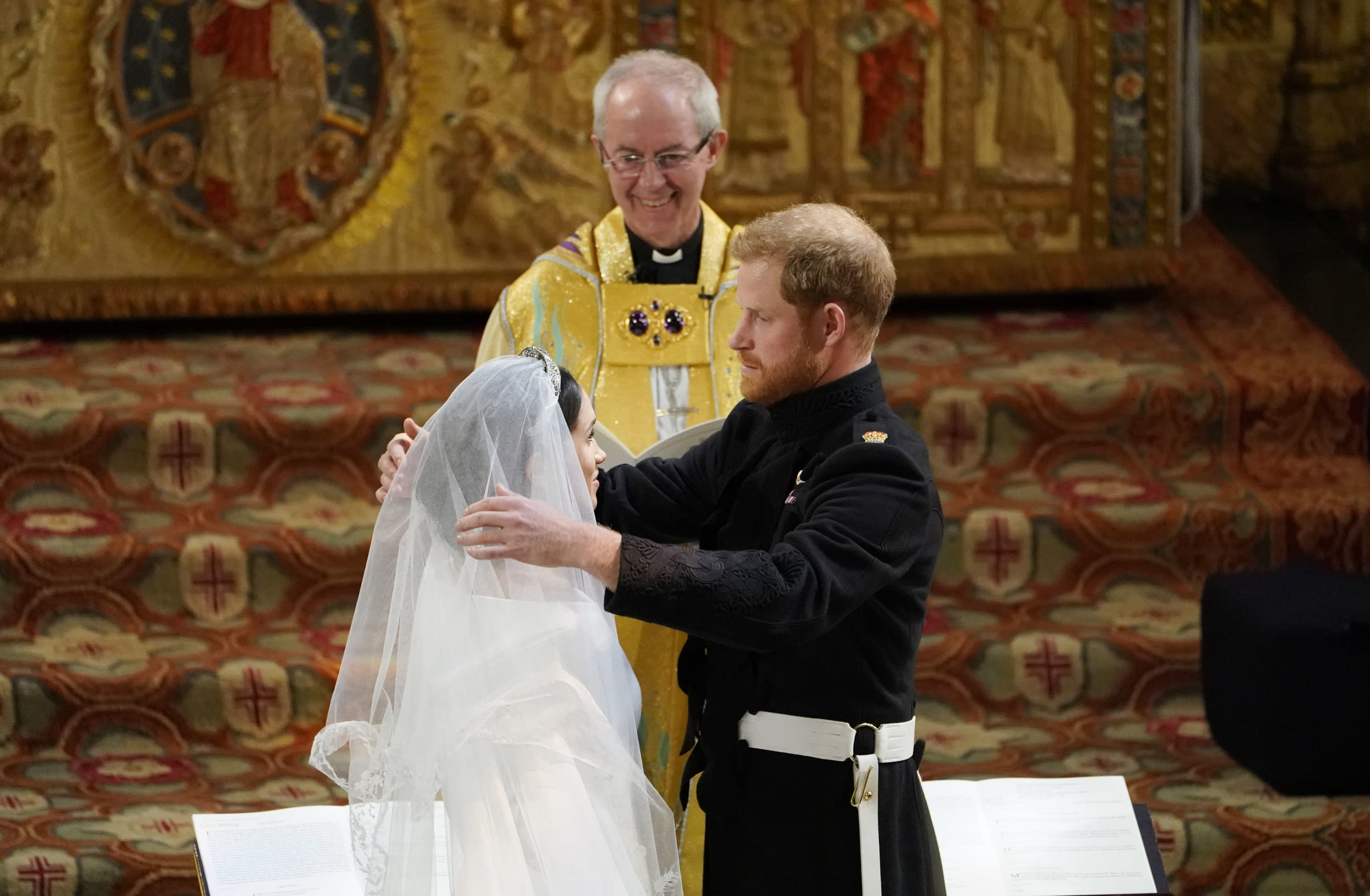 TOPSHOT - Britain's Prince Harry, Duke of Sussex (R) removes the veil of US actress Meghan Markle (L) as they stand at the altar together before Archbishop of Canterbury Justin Welby (C) in St George's Chapel, Windsor Castle, in Windsor, on May 19, 2018 during their wedding ceremony. (Photo by Owen Humphreys / POOL / AFP)        (Photo credit should read OWEN HUMPHREYS/AFP/Getty Images)