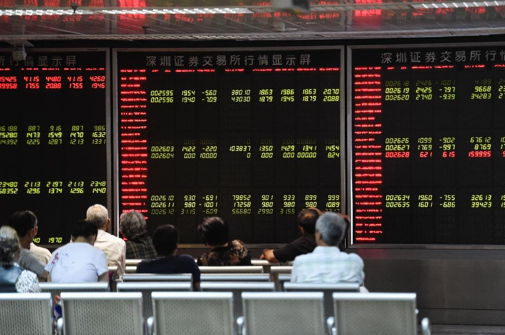 Investors look at screens showing stock market movements at a securities company in Beijing, China, on August 25, 2015 (AFP Photo/Fred Dufour)