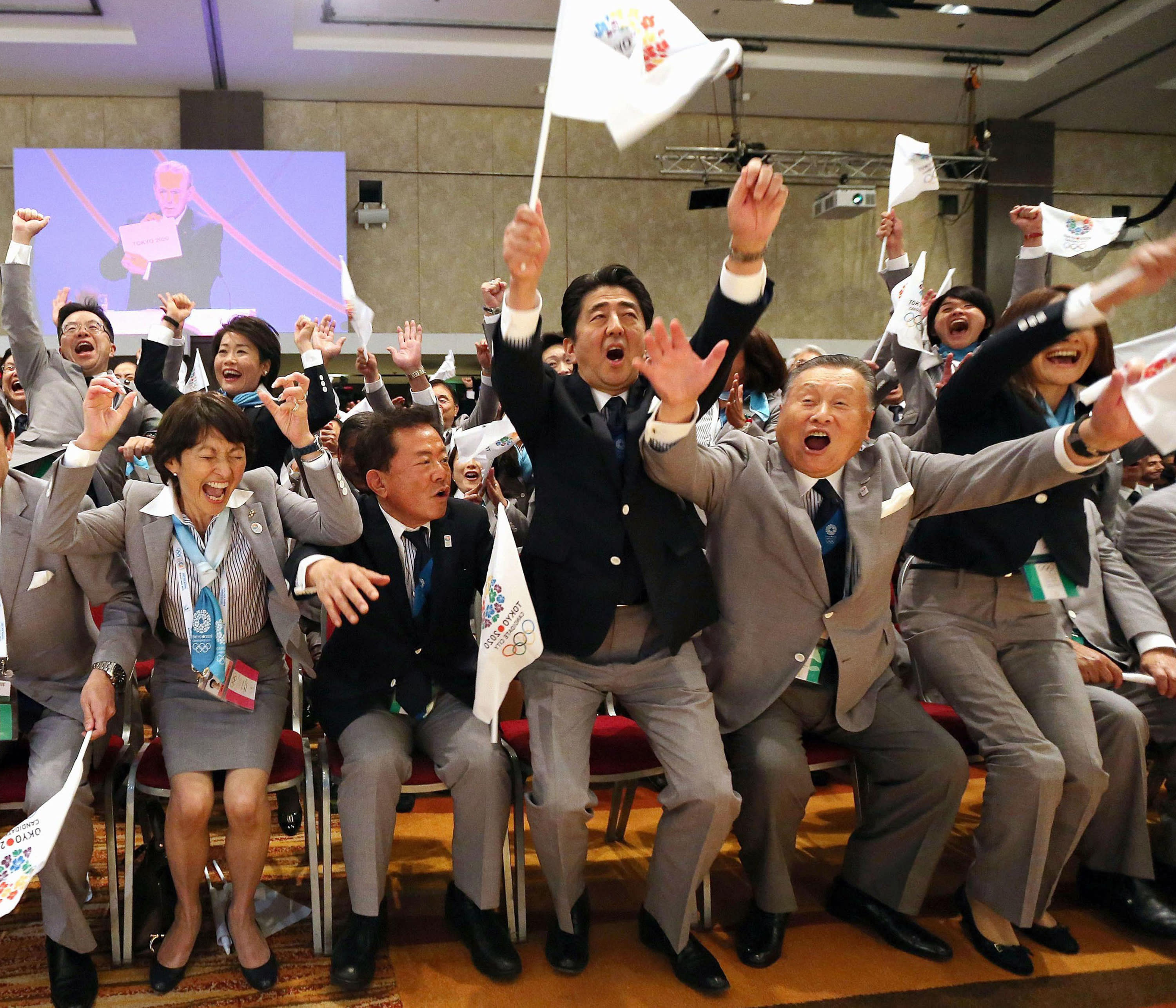 FILE - In this Sept. 7, 2013, file photo, Japanese Prime Minister Shinzo Abe, center, and former prime minister Yoshiro Mori, right, with other delegates, celebrate after Tokyo was awarded the 2020 Summer Olympic Games, in Buenos Aires, Argentine. Abe was in the front row in 2013 in Buenos Aires when IOC President Jacques Rogge opened an envelop to show Tokyo was the 2020 host, beating out Istanbul. (Kyodo News via AP, File)