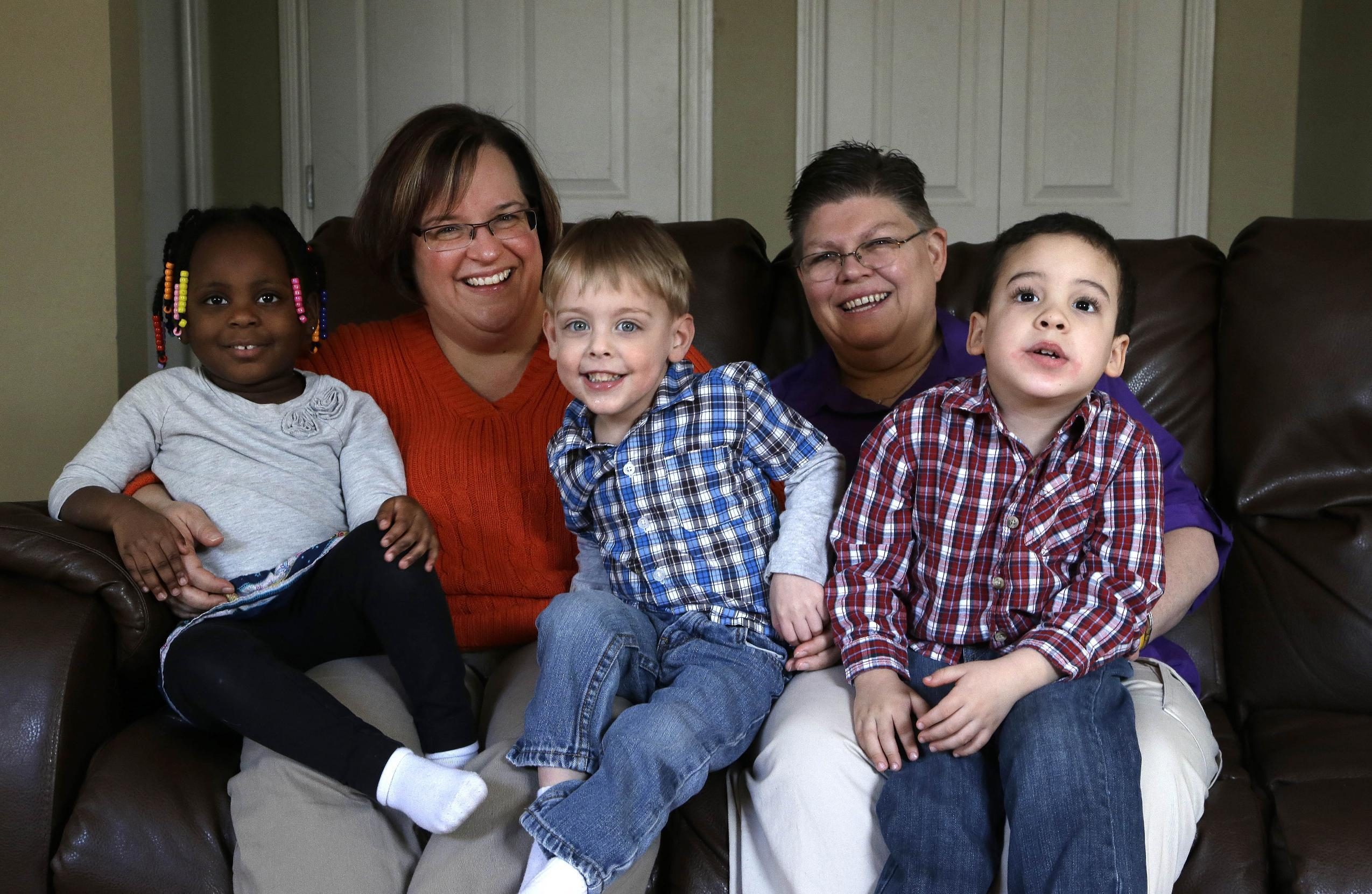 April DeBoer, second from left, sits with her adopted daughter Ryanne, 3, left, and Jayne Rowse, fourth from left, and her adopted sons Jacob, 3, middle, and Nolan, 4, right, at their home in Hazel Park, Tuesday, March 5, 2013. The lesbian couple's desire to adopt each other's children has grown into a potentially ground-breaking challenge to Michigan's ban on same-sex marriage. The two Detroit-area nurses filed a lawsuit to try to overturn restrictions on adoption by same-sex partners. But at the judge's invitation, the case has taken an extraordinary turn and now will test the legality of a 2004 constitutional amendment that says only marriage of a man and woman is recognized in Michigan. (AP Photo/Paul Sancya)