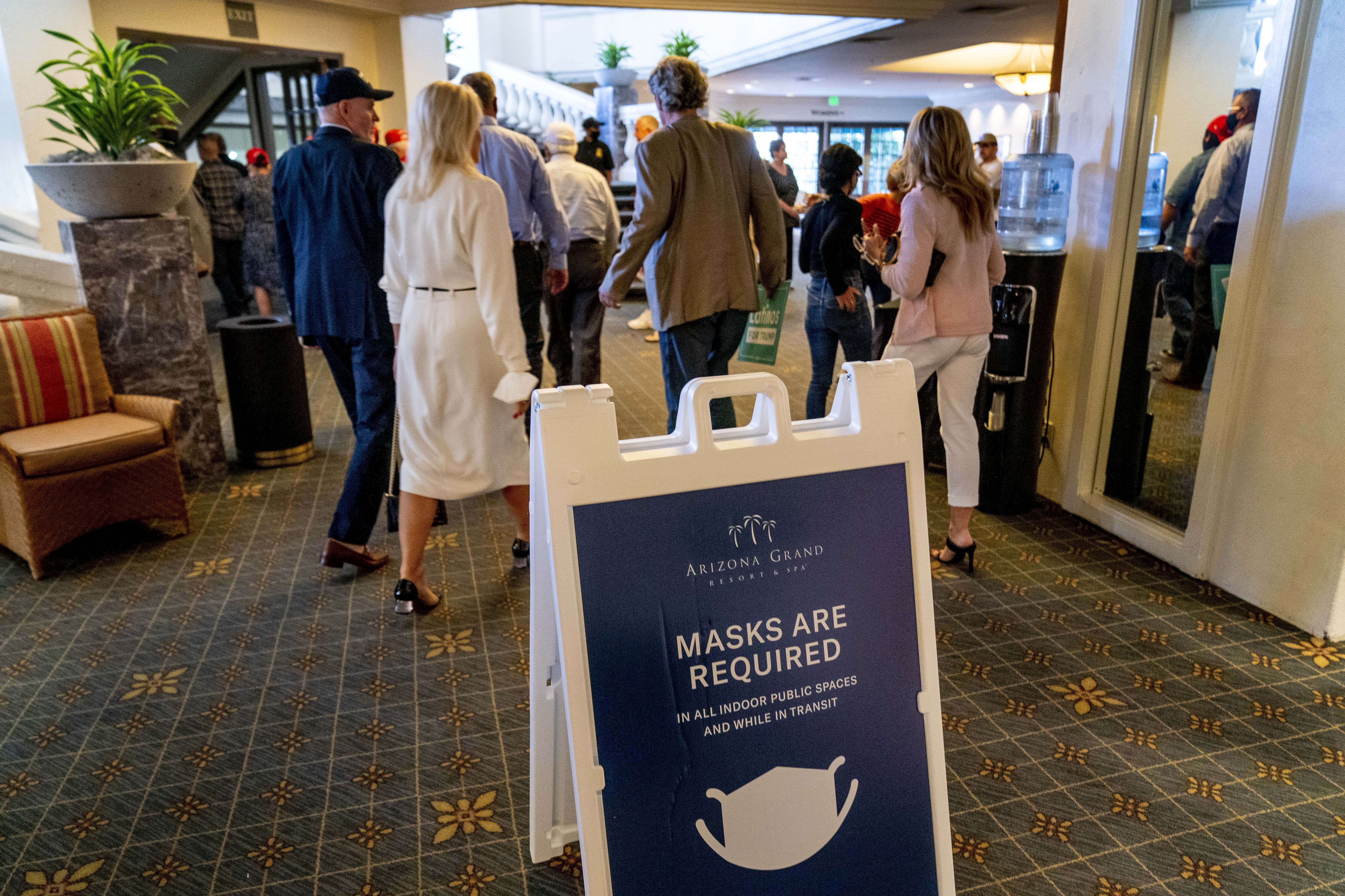 """A sign reads """"Masks Are Required"""" outside a Latinos for Trump Coalition roundtable where President Donald Trump spoke at Arizona Grand Resort & Spa, Monday, Sept. 14, 2020, in Phoenix. (AP Photo/Andrew Harnik)"""