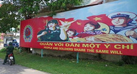 A soldier stands parks his motorcycle in front of a banner at the headquarters of the Division 308 special military force in Xuan Mai town, outside Hanoi July 10, 2015. REUTERS/Greg Torode