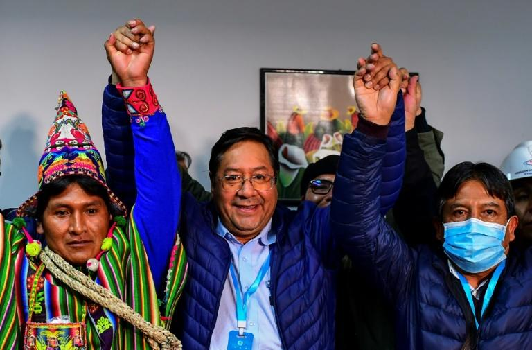 Luis Arce (center) celebrates with running mate David Choquehuanca (right) after exit poll results come in