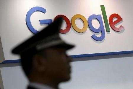 A security guard keeps watch as he walks past a logo of Google in Shanghai