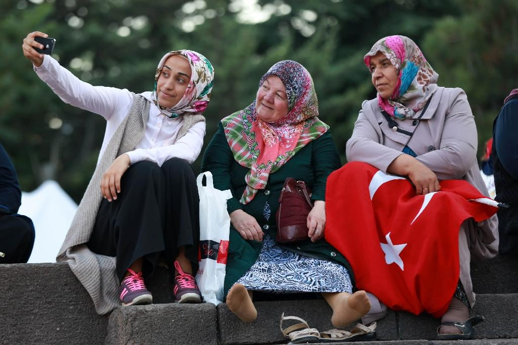 Women pose for a selfie as they attend a rally against the military coup at Kizilay Square in Ankara (AFP Photo/Adem Altan)