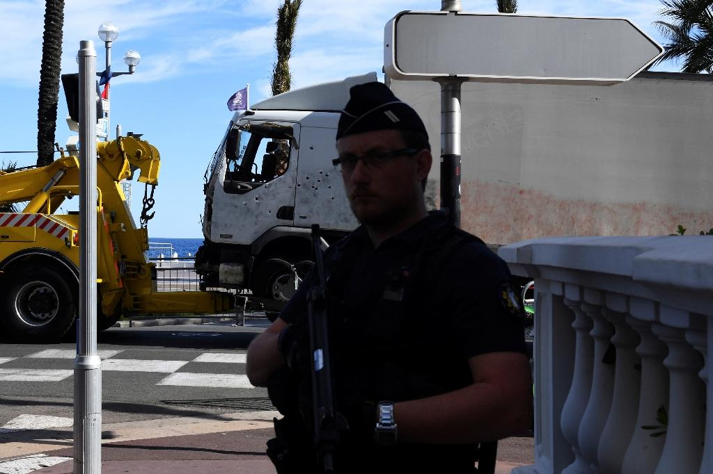A French police officer stands guard as the truck that was driven through a crowd celebrating Bastille Day is towed away in Nice, on July 15, 2016 (AFP Photo/Boris Horvat)