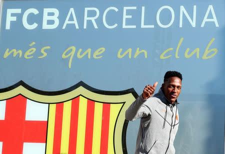 El futbolista colombiano Yerry Mina posa frente al escudo del FC Barcelona en las oficinas del club