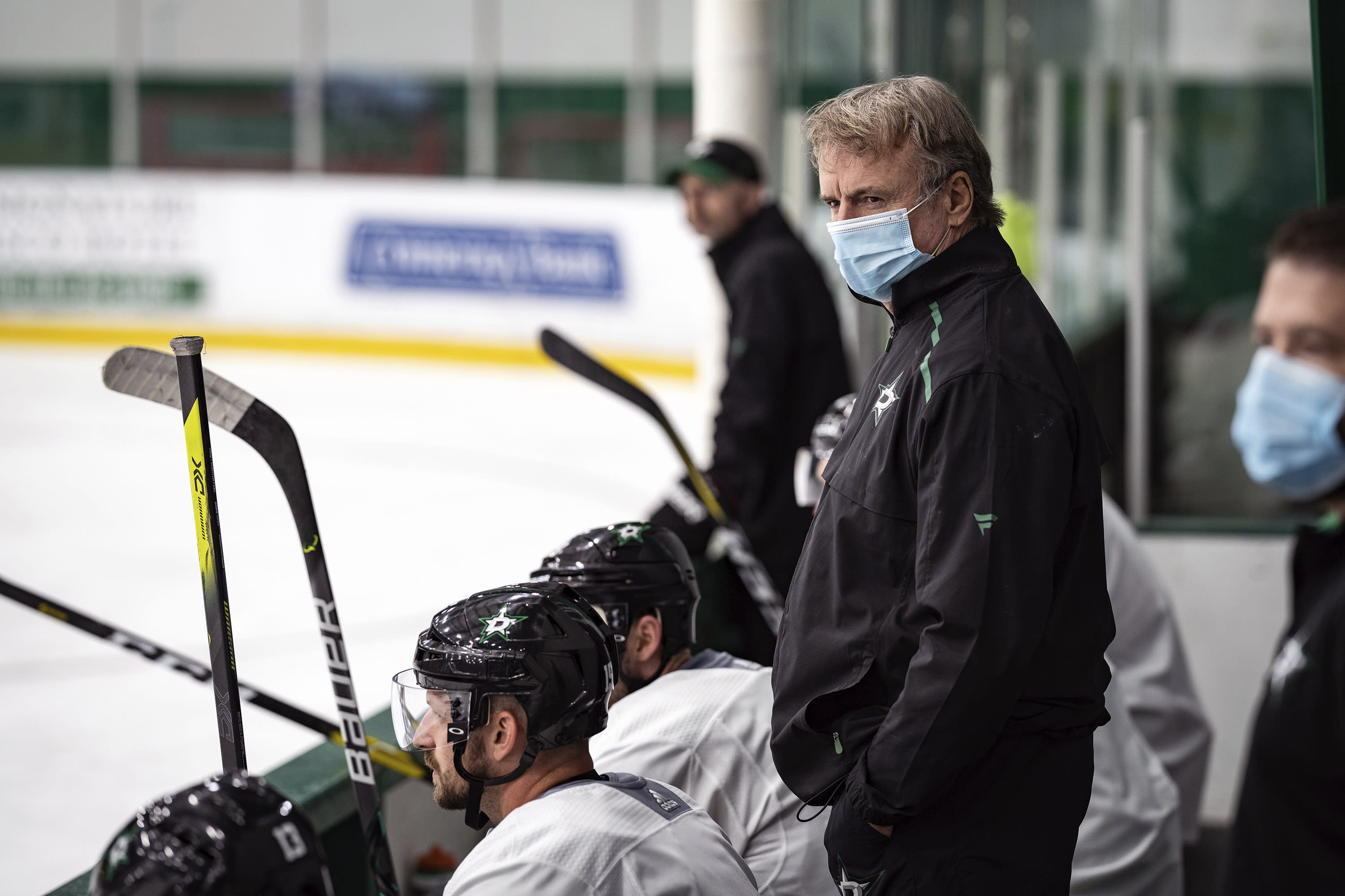 In this photo provided by the Dallas Stars NHL hockey team, interim head coach Rick Bowness watches practice in Frisco, Texas, Tuesday, July 14, 2020. Bowness, 65, coached from behind the bench the first couple of days of Dallas Stars training camp before lacing up his skates and getting on the ice. Montreal's 60-year-old Claude Julien, Edmonton's 58-year-old Dave Tippett and others are confident in the NHL's protocols as older, more at-risk people during the COVID-19 pandemic. (Jeff Toates/Dallas Stars via AP)