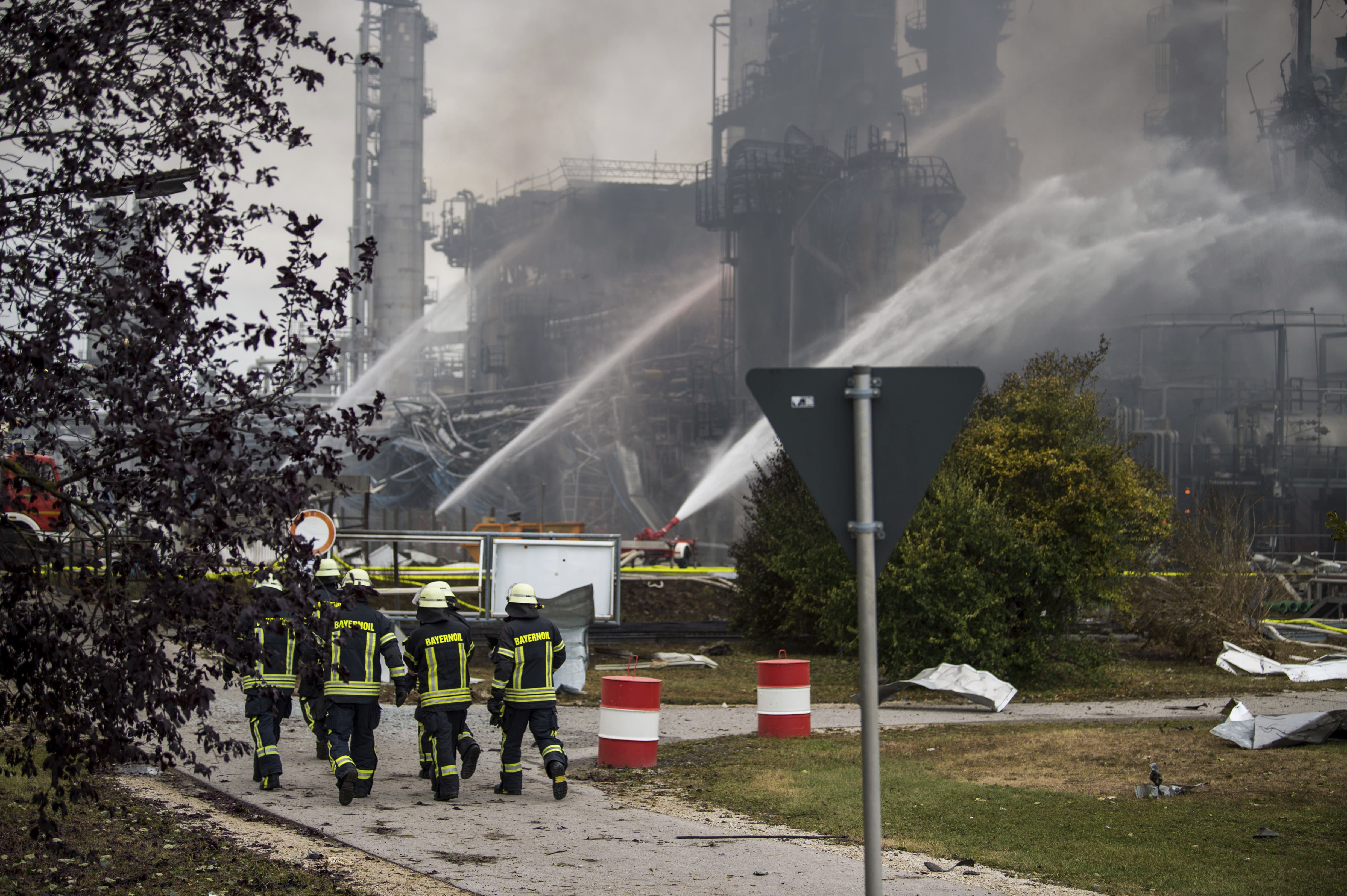 Firefighters walk over the area of a Bayernoil refinery in Vohburg an der Donau near Ingolstadt, southern Germany, Saturday, Sept. 1, 2018 after a fire broke out. (Lino Mirgeler/dpa via AP)