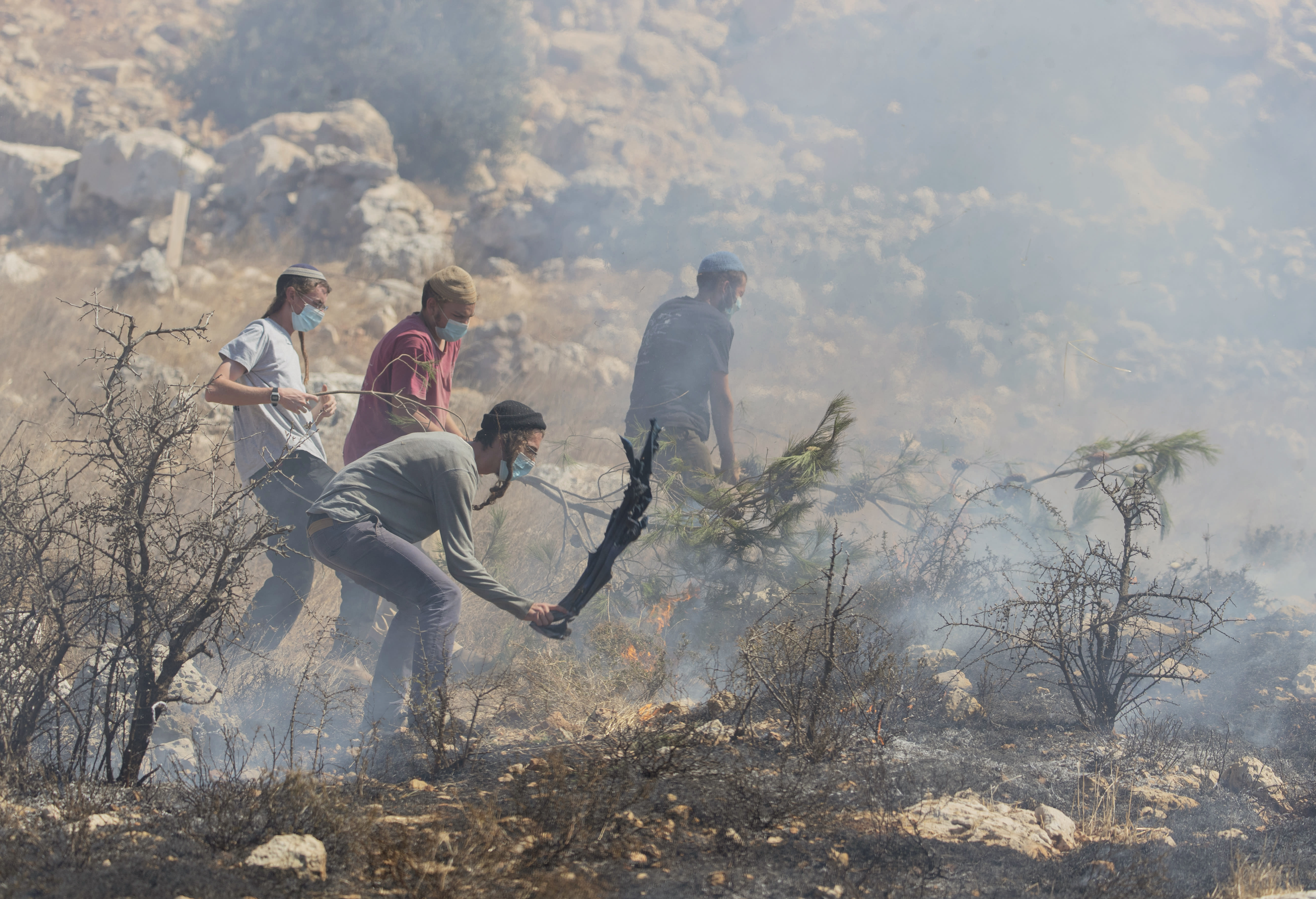 Jewish settlers fight fire in olive groves near their outpost that was caused by Israeli police's teargas canisters, used to disperse Palestinian farmers going to their groves, in the West Bank village of Burqa, East of Ramallah, Friday, Oct. 16, 2020. Palestinians clashed with Israeli border police in the West Bank on Friday during their attempt to reach and harvest their olive groves near a Jewish settlers outpost. (AP Photo/Nasser Nasser)