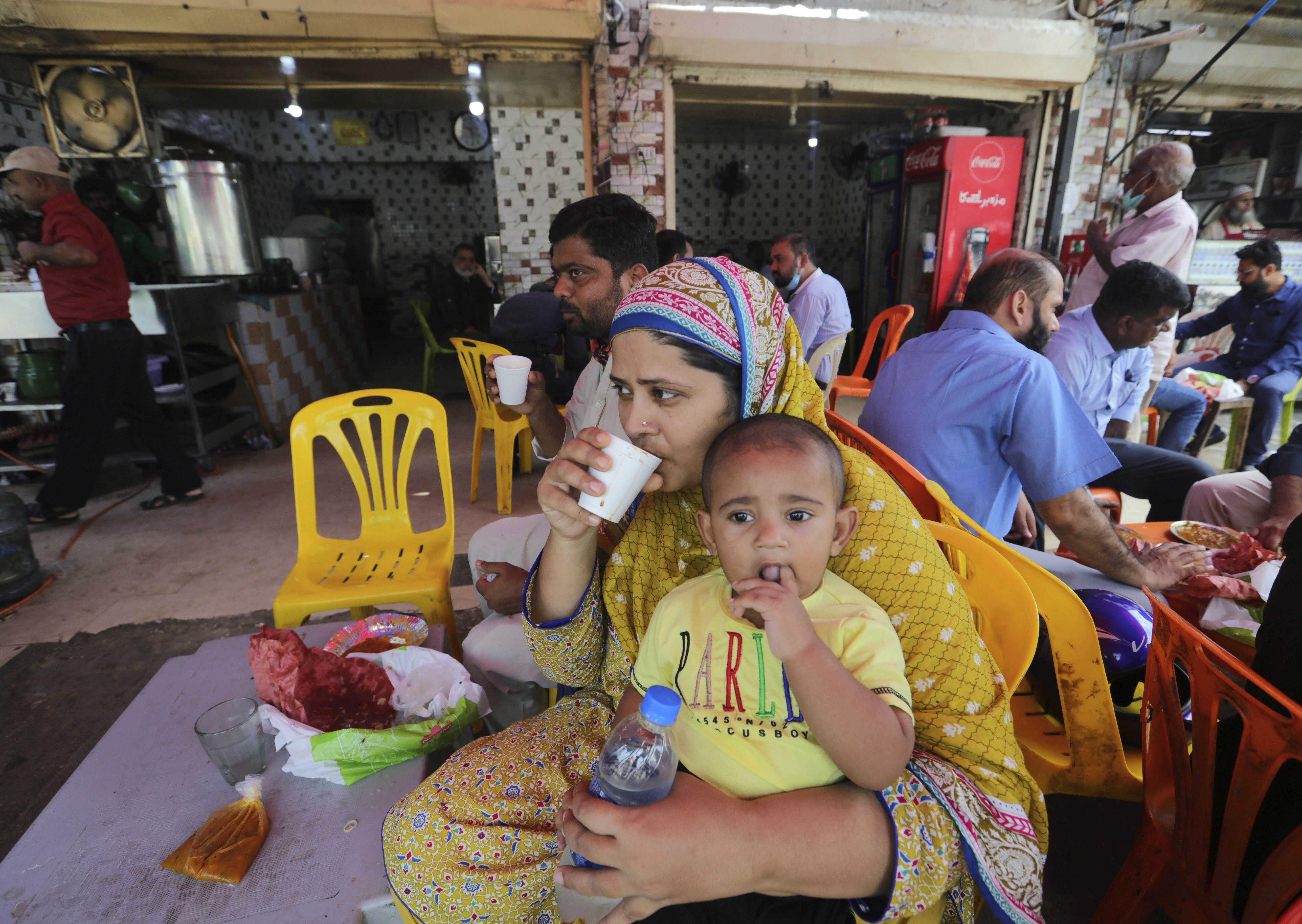 People eat at a restaurant following an ease in restrictions that had been imposed to help control the coronavirus, in Karachi, Pakistan, Monday, Aug. 10, 2020. Pakistan's daily virus infection rate has stayed under 1,000 for more than four weeks prompting the government to further ease restrictions for restaurants, parks, gyms and cinemas. (AP Photo/Fareed Khan)