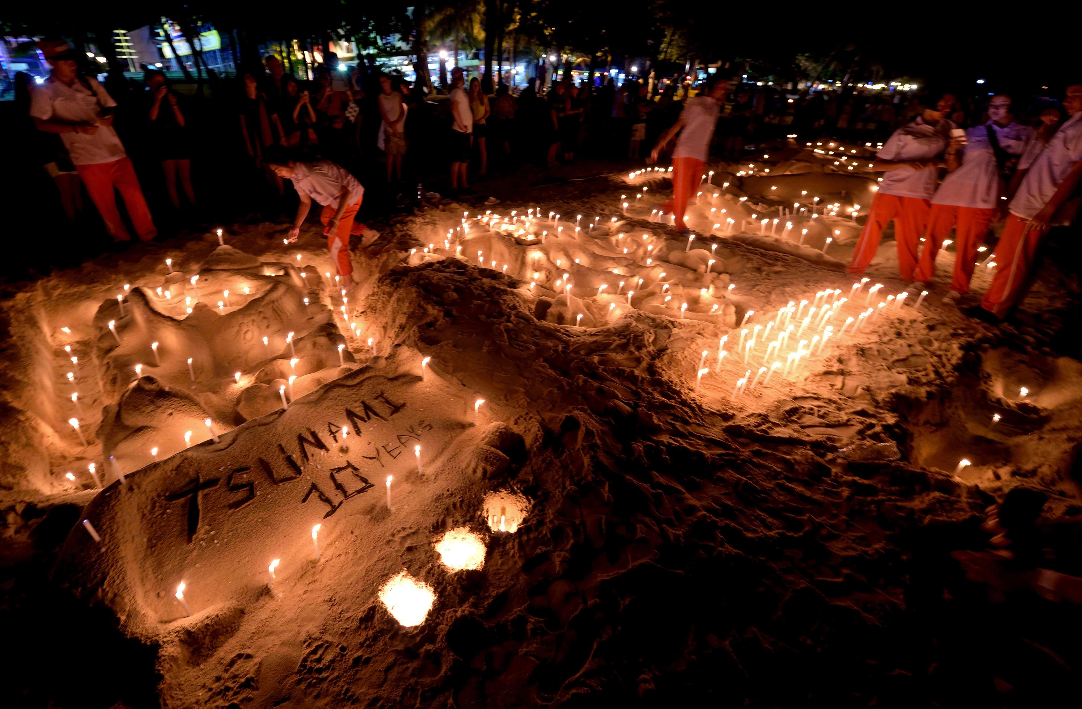 Thai students place candles on a sand sculpture during commemorations on the the tenth anniversary of the 2004 tsunami at Patong beach in Phuket province on December 26, 2014 (AFP Photo/Pornchai Kittiwongsakul)