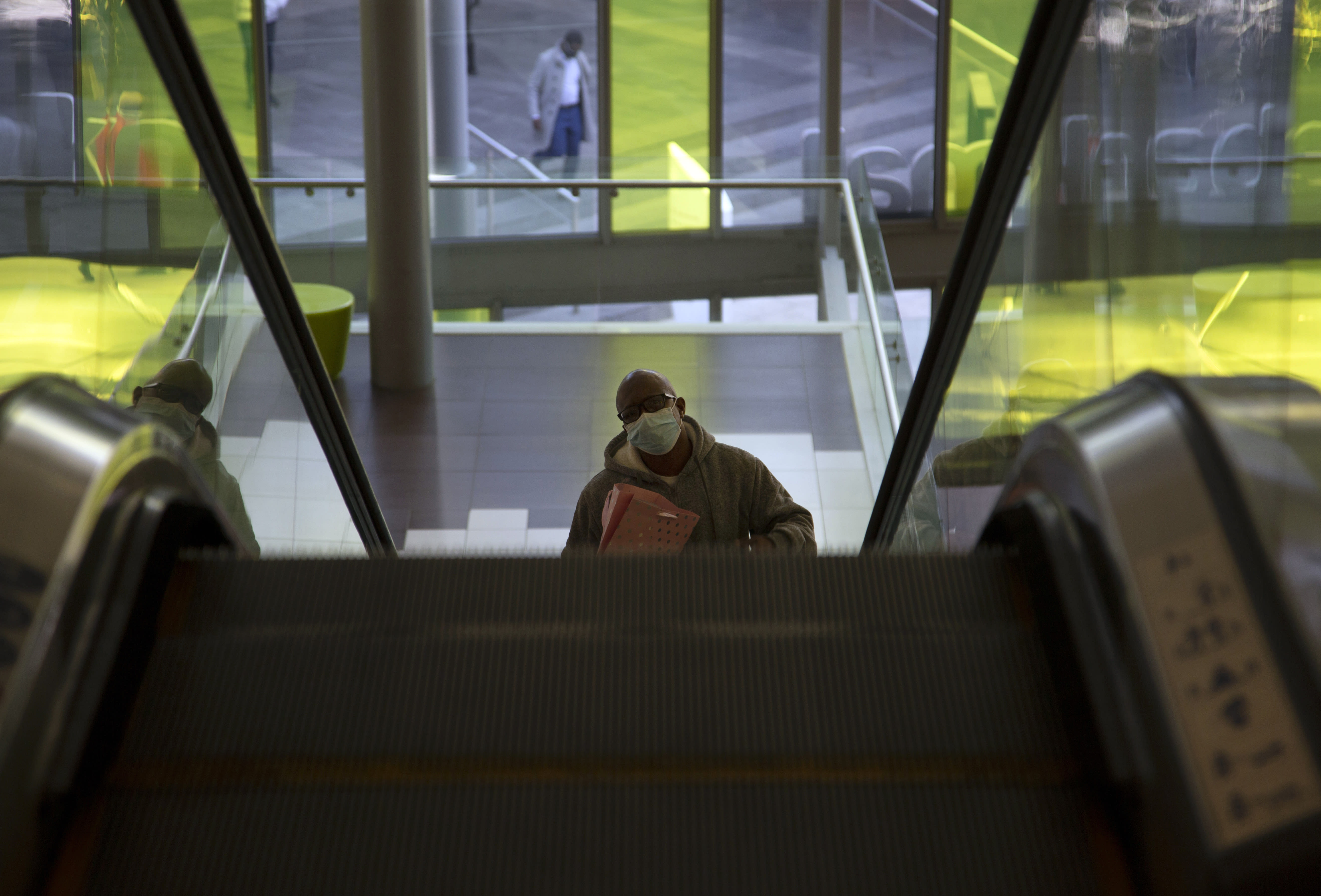 A masked man rides on an escalator in a mall in Johannesburg, Tuesday, July 14, 2020. The government has ruled it compulsory for people to wear face coverings in a bid to control the spread of COVID-19 as the country heads towards its coronavirus peak. (AP Photo Denis Farrell)