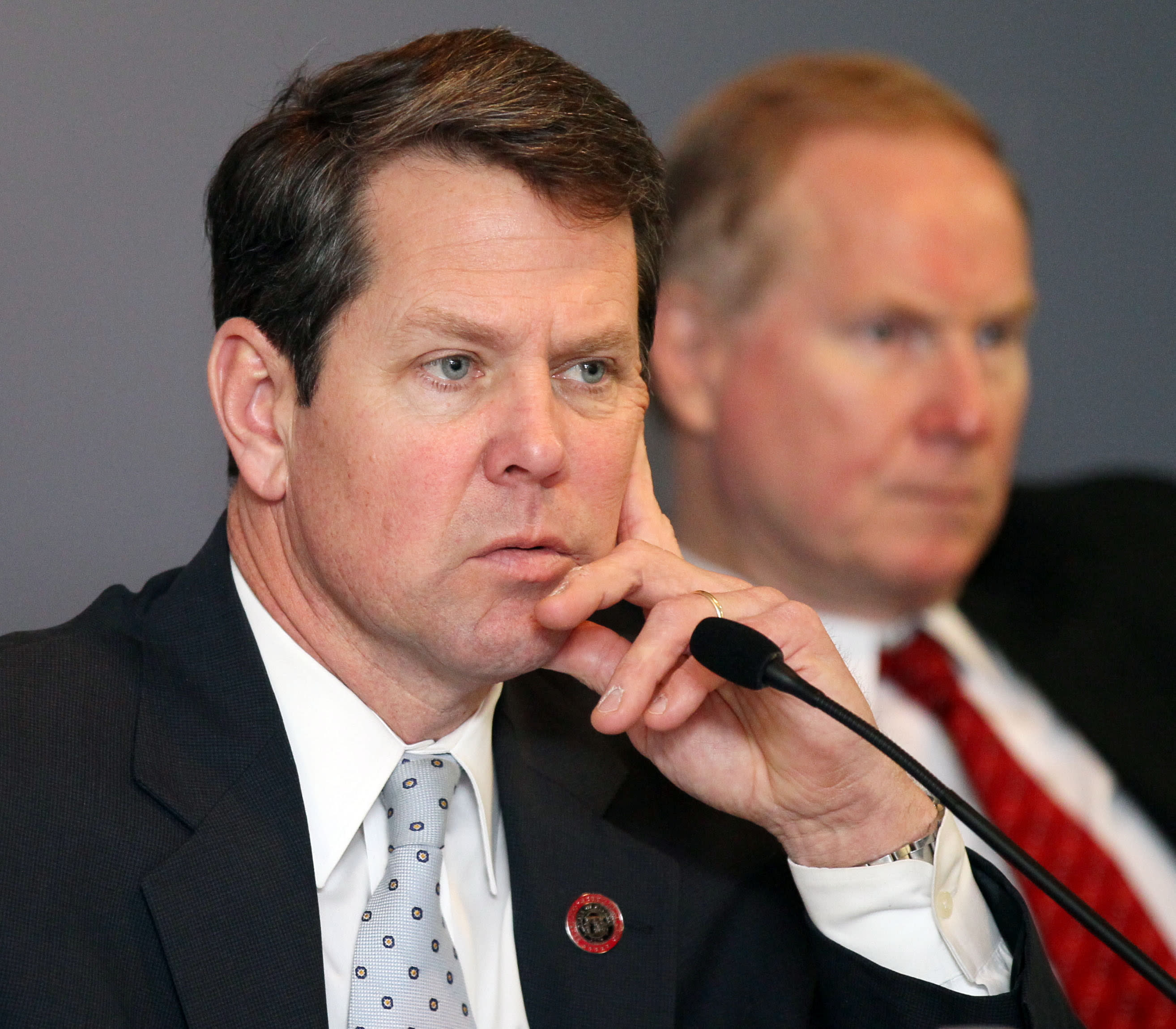 Georgia Secretary of State Brian Kemp, left, and State Election Board member L. Kent Webb listen as investigators grill Fulton County elections officials on problems with last years presidential elections during a hearing at the Sloppy Floyd building in Atlanta on Thursday, Jan. 31, 2013. A statewide spotlight will be cast on Fulton County's incompetence Thursday when the State Election Board holds a hearing, somewhere at the state Capitol complex, on recent elections problems. Secretary of State Brian Kemp fast-tracked investigations into more than 100 complaints about Fulton's polling problems during last year's presidential contest. The election board, which he chairs, will decide whether to reprimand the county or send cases on to the state Attorney General for possible prosecution. (Phil Skinner/Atlanta Journal-Constitution via AP)