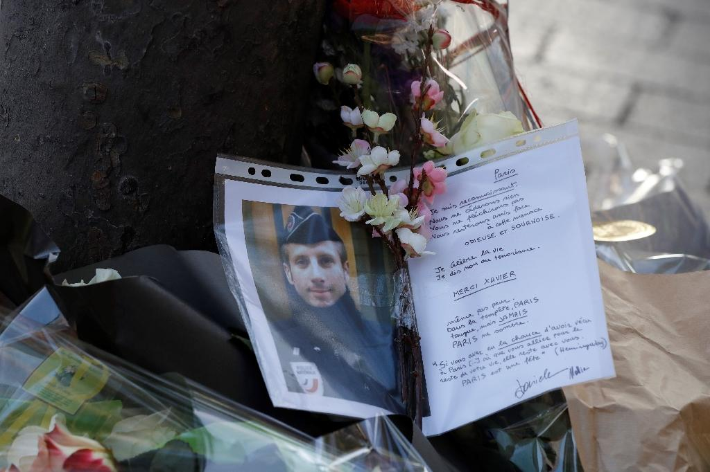 A photo and a letter displayed at the site of a shooting on the Champs Elysees which left one police officer dead and wounded two others (AFP Photo/FRANCOIS GUILLOT)