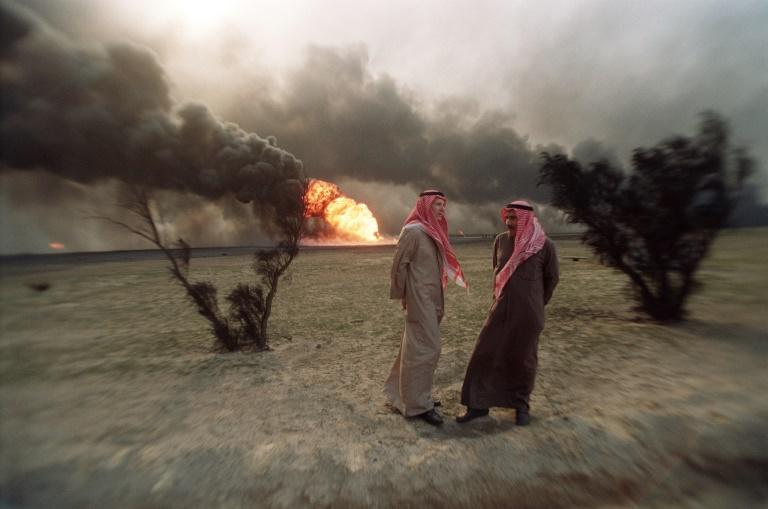 Two Kuwaiti men walk in the al-Ahmadi oil field, where wells were set ablaze by retreating Iraqi troops, in March 1991 (AFP Photo/MICHEL GANGNE)