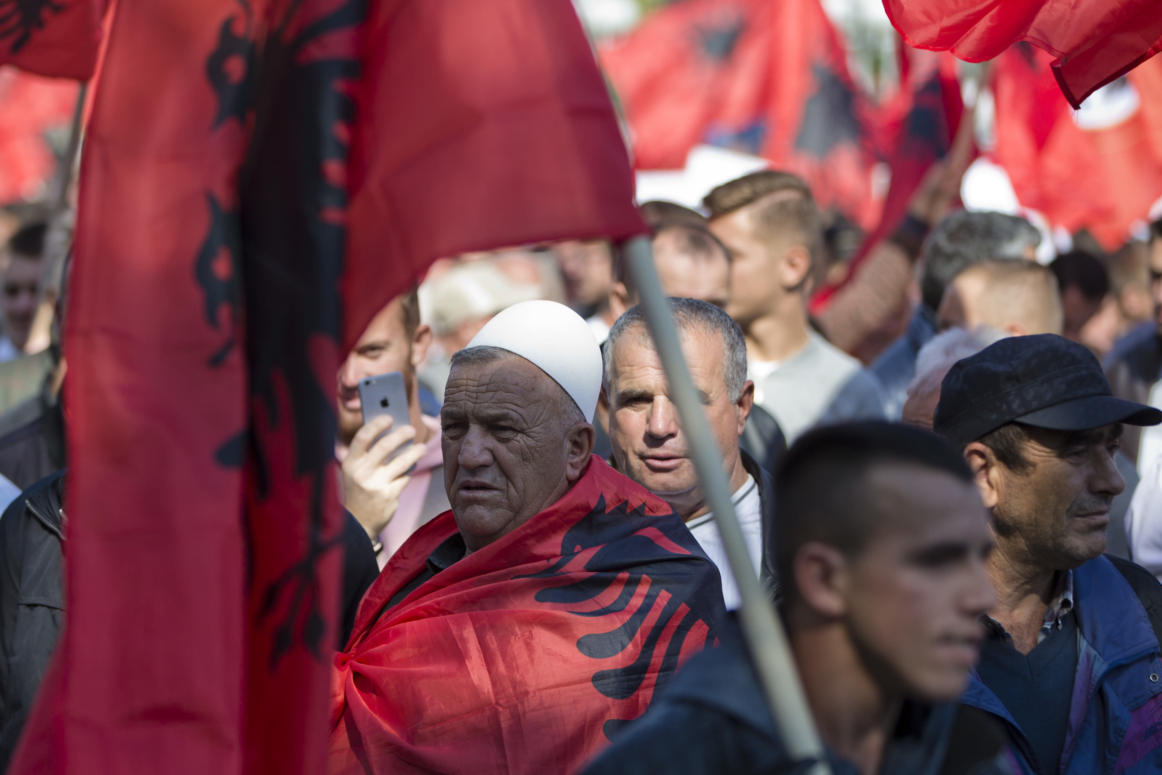 Supporter of Kosovo's opposition Self-Determination party draped with national Albanian flag marches during a protest toward Skanderbeg Square on Saturday, Sept. 29, 2018, in Kosovo capital Pristina. Thousands of people in Kosovo are protesting their president's willingness to include a possible territory swap with Serbia in the ongoing negotiations to normalize relations between the two countries.(AP Photo/Visar Kryeziu)