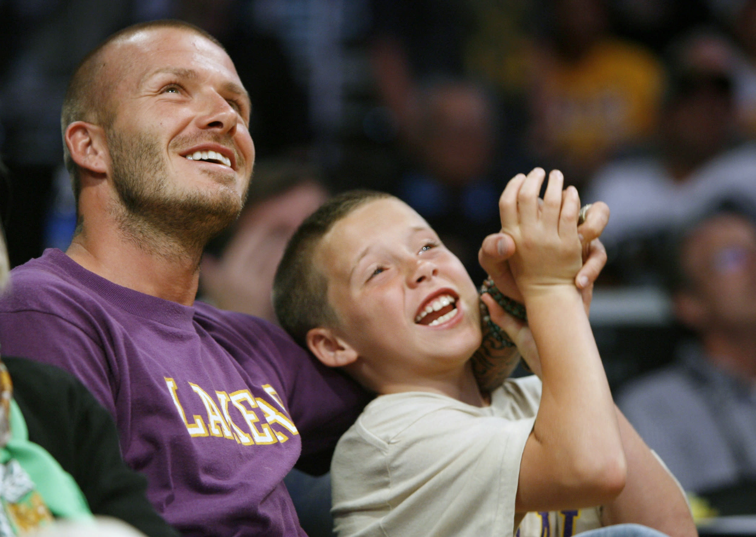 Soccer star David Beckham sits with his son Brooklyn while the Los Angeles Lakers play the Boston Celtics during Game 3 of the NBA Finals basketball championship in Los Angeles, June 10, 2008.     REUTERS/Jeff Haynes (UNITED STATES)