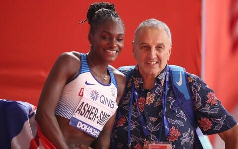 Dina Asher-Smith of Great Britain celebrates after winning gold in the Women's 200 metres final with coach John Blackie - Credit: Christian Petersen/Getty Images