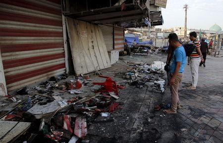 People inspect the site of car bomb in New Baghdad, July 22, 2015. REUTERS/Khalid al-Mousily