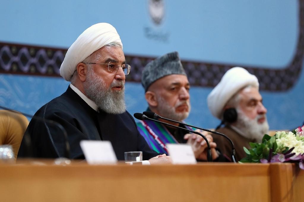 Iranian President Hassan Rouhani urges Muslim unity against the United States at a conference in Tehran attended by former Afghan president Hamid Karzai (C) and the deputy head of Lebanon's Hezbollah, Sheikh Naim Qassem