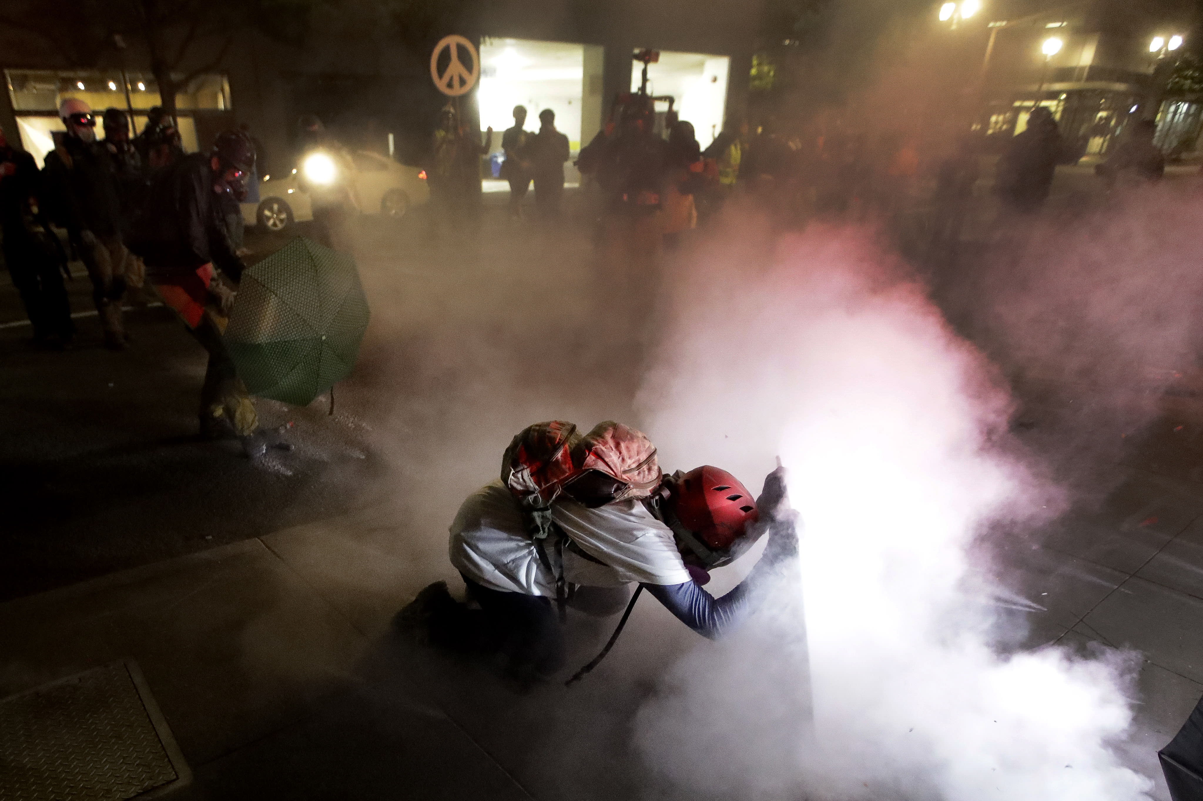 A demonstrator kneels and uses a makeshift shield as federal agents launch tear gas during a Black Lives Matter protest at the Mark O. Hatfield United States Courthouse Wednesday, July 29, 2020, in Portland, Ore. (AP Photo/Marcio Jose Sanchez)