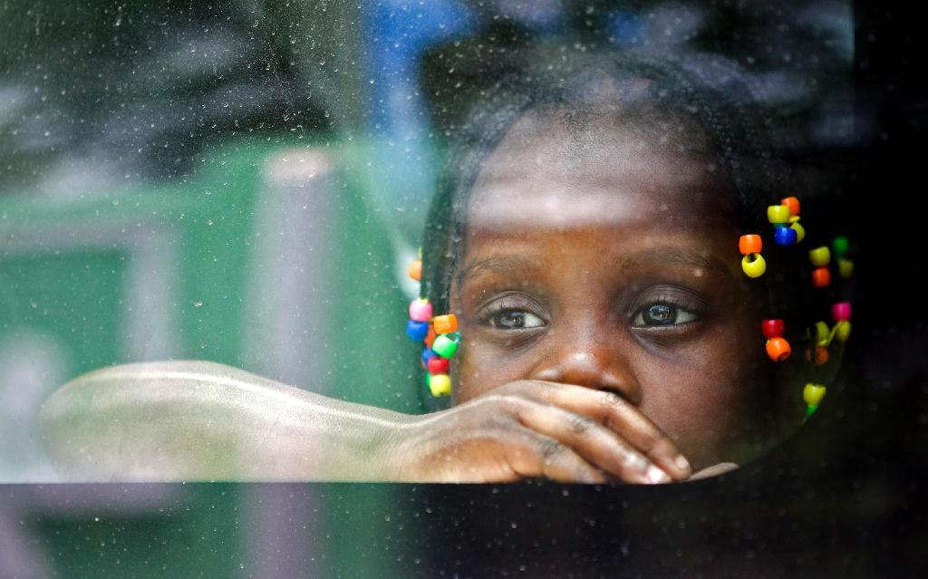An Haitian girl looks from the window of a vehicle as her family is transported to be voluntarily repatriated in Santo Domingo, Dominican Republic, on June 29, 2015 (AFP Photo/Erika Santelices)