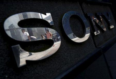 Pedestrians are reflected in a logo of Sony Corp outside its showroom in Tokyo
