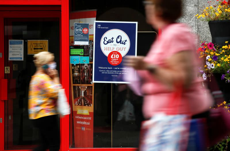 """FILE PHOTO: People walk past a take-out restaurant with an """"Eat out to help out"""" poster in the window, in Luton"""