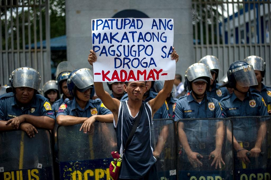 An activist holds a banner in front of Philippine National Police headquarters during a protest condemning extra-judicial killings related to President Rodrigo Duterte's campaign against drugs, in Manila, on August 24, 2016