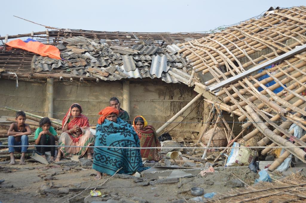 A Nepali family sits in front of their damaged home in the southern Bara district after a freak storm wreaked devastation in the region (AFP Photo/DIWAKAR BHANDARI)