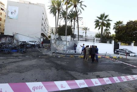 People and security stand at the scene of a car bomb explosion near the Egyptian embassy in the Libyan capital of Tripoli November 13, 2014. REUTERS/Stringer