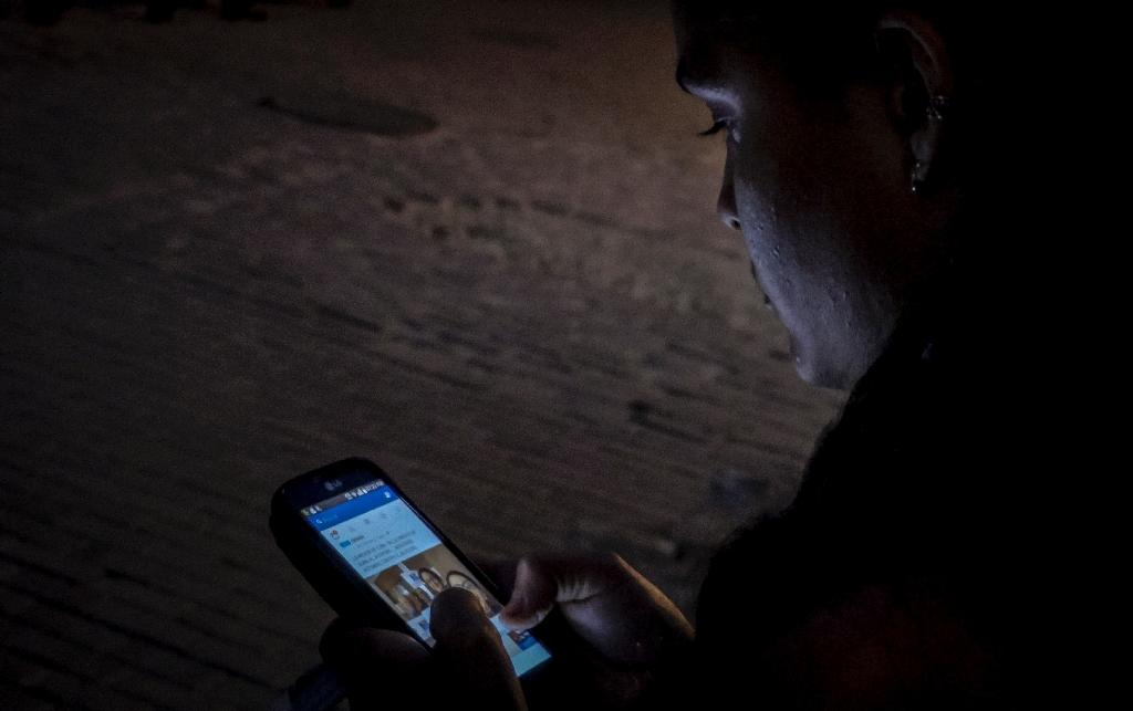 A woman uses public WiFi to connect her phone in a street of Havana (AFP Photo/Adalberto Roque)