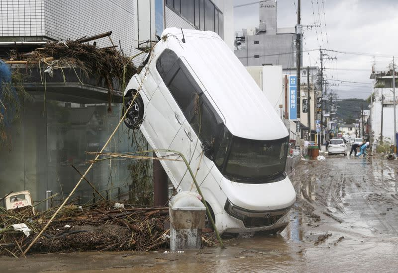 A car is pictured after it was drifted by torrential rain in Hitoyoshi