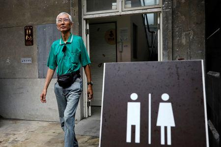 "Chi Chia-wei, 59, a gay rights activist, leaves a bathroom in Taipei. ""If Taiwan refuses to improve, we will continue our efforts and make a rainbow country. Even a revolution,"" he said. REUTERS/Tyrone Siu"