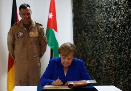 German Chancellor Angela Merkel writes in a book as she visits German soldiers stationed in Jordan, June 21, 2018. REUTERS/Muhammad Hamed