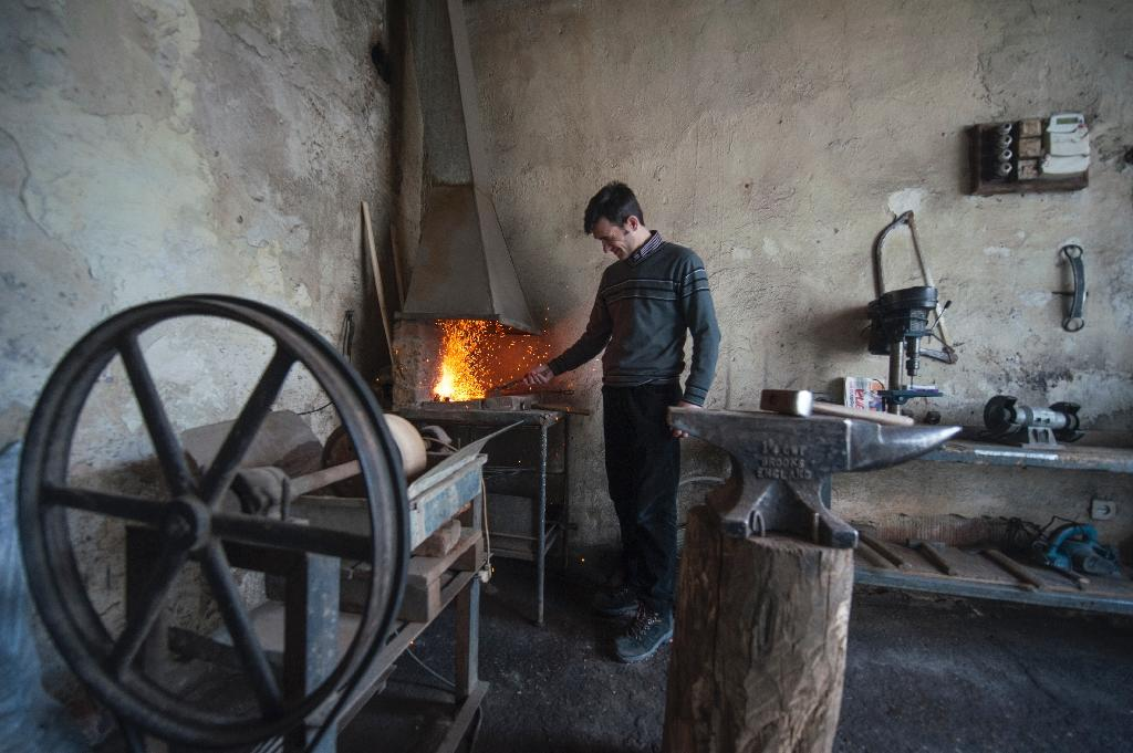 A Kosovo Albanian blacksmith works on agricultural tools at his small workshop near the town of Pristina on March 16, 2015 (AFP Photo/Armend Nimani)