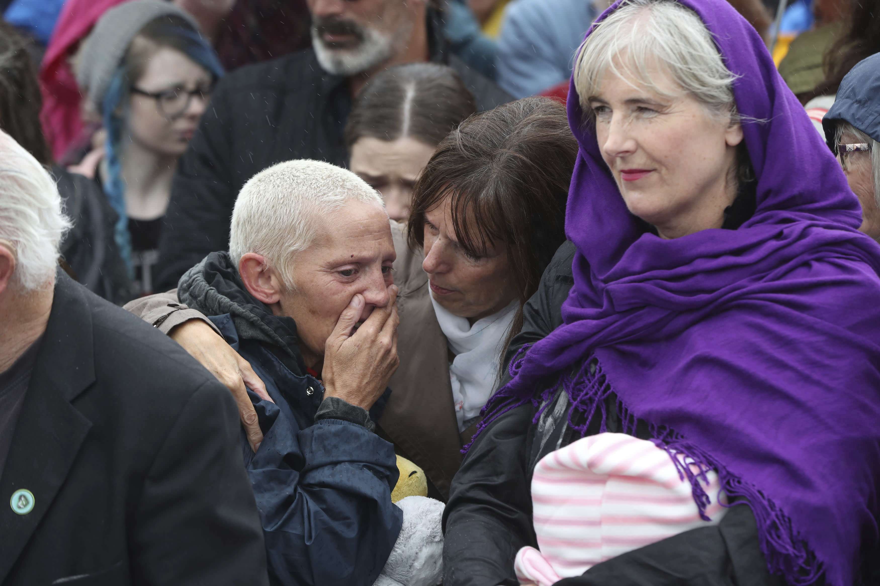 People gather to protest at the site of the former Tuam home for unmarried mothers in County Galway, during the visit to Ireland by Pope Francis, Sunday, Aug. 26, 2018. Survivors of one of Ireland's wretched mother and baby homes were to hold their own demonstration Sunday. The location is Tuam, site of a mass grave of hundreds of babies who died at a church-run home. (Niall Carson/PA via AP)