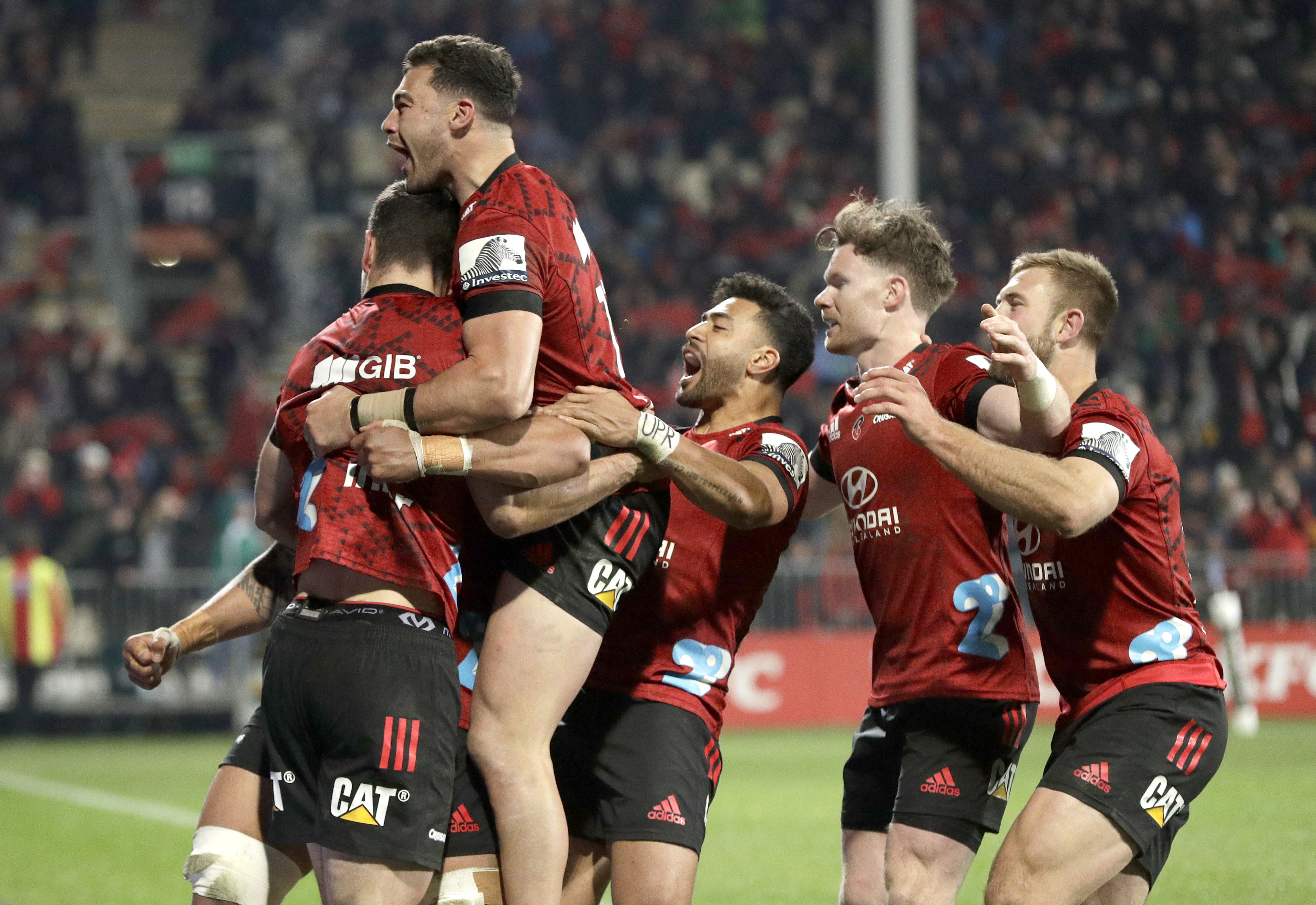 Crusaders Will Jordan, left, is congratulated by teammates after scoring his team's match winning try during the Super Rugby Aotearoa rugby game between the Crusaders and the Blues in Christchurch, New Zealand, Saturday, July 11, 2020. (AP Photo/Mark Baker)