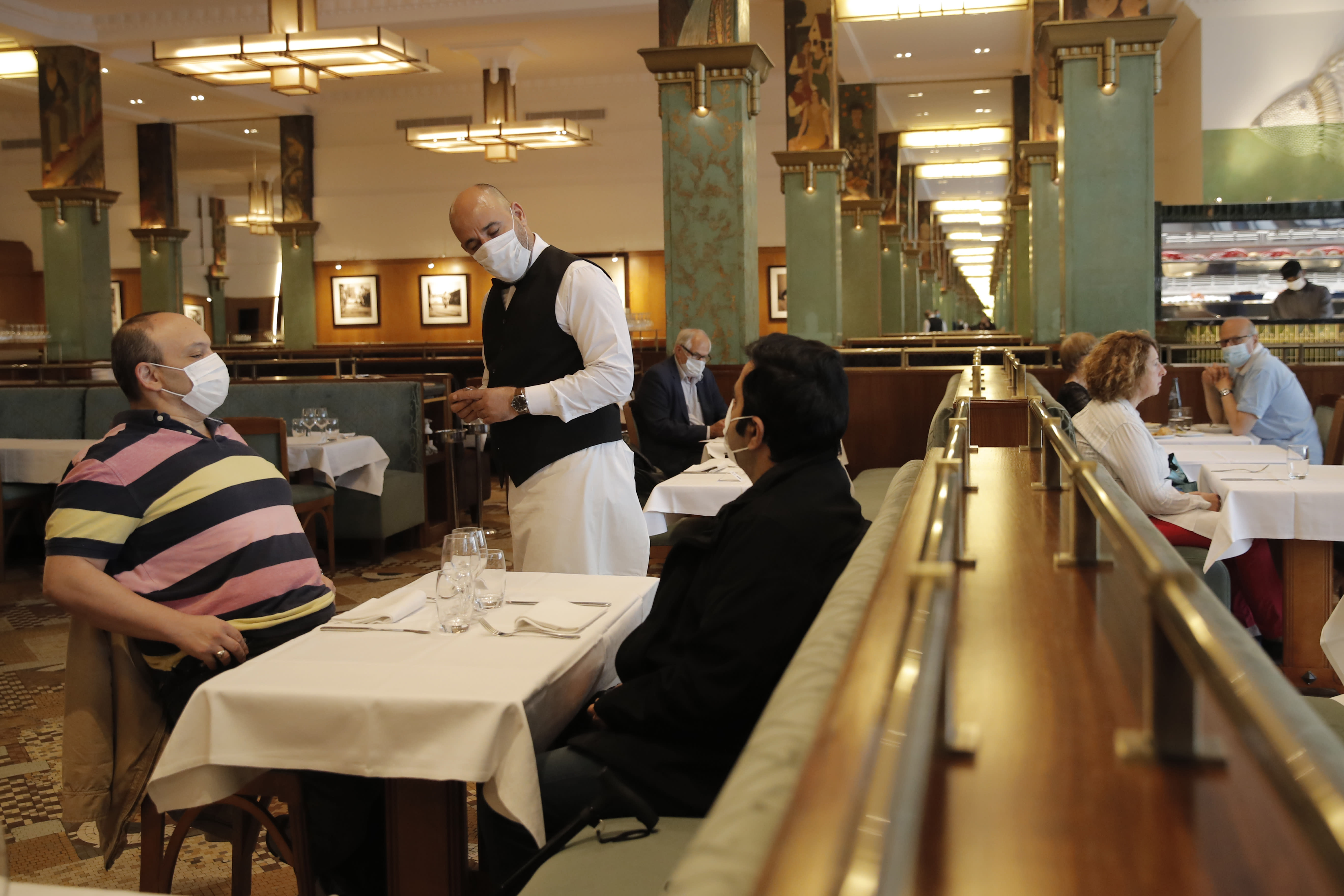A waiter listens to clients at La Coupole restaurant, Monday, June 15, 2020 in Paris. Paris is rediscovering itself, as its cafes and restaurants reopen for the first time since the fast-spreading virus forced them to close their doors March 14. Restaurants outside the Paris region opened earlier this month, and Paris cafes were allowed to serve people outside but not open their doors. After three months of losses, some restaurateurs fear it will take a long time for business to come back. (AP Photo/Christophe Ena)