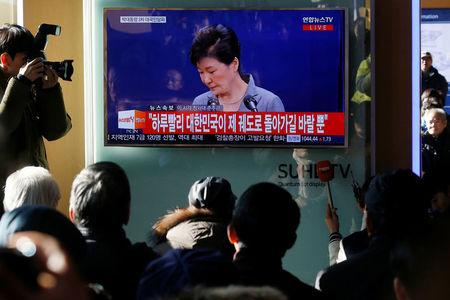 People watch a television broadcast of a news report on President Park Geun-hye releasing a statement to the public in Seoul, South Korea, November 29, 2016. REUTERS/Kim Hong-Ji