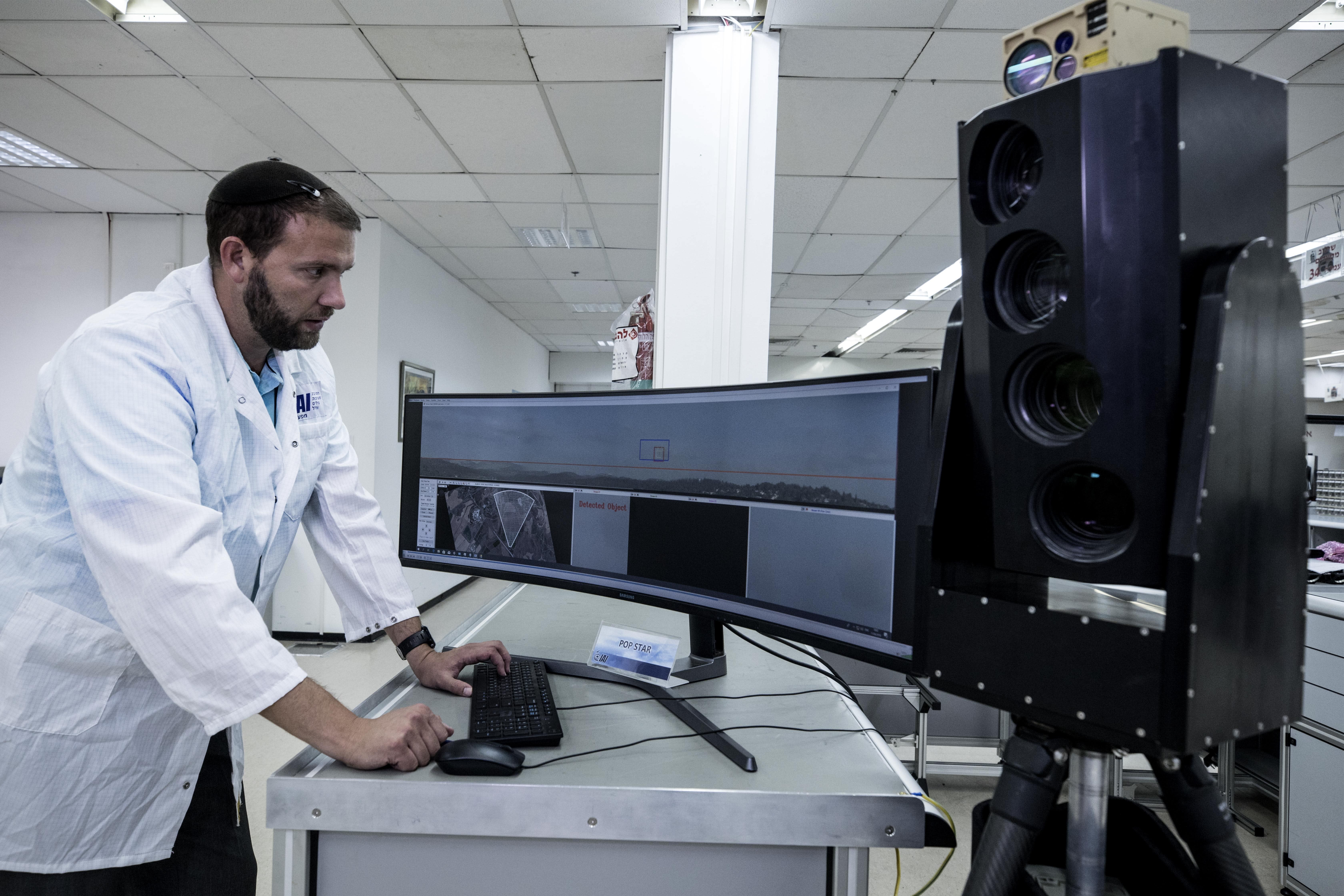 In this Monday, Sept. 9, 2019 photo, Ariel Gomez, a systems engineer at Israel Aerospace Industries, works on the Popstar system that can track and identify flying objects day or night without being detected, at Israel Aerospace Industries, in the Israeli town of Yehud near Tel Aviv. Israel has long been a dominant player in the military drone export business, developing small attack aircraft as well as long-range spy planes. Now, Israeli firms are at the forefront of a global industry developing means to protect against the drone threat. (AP Photo/Tsafrir Abayov)