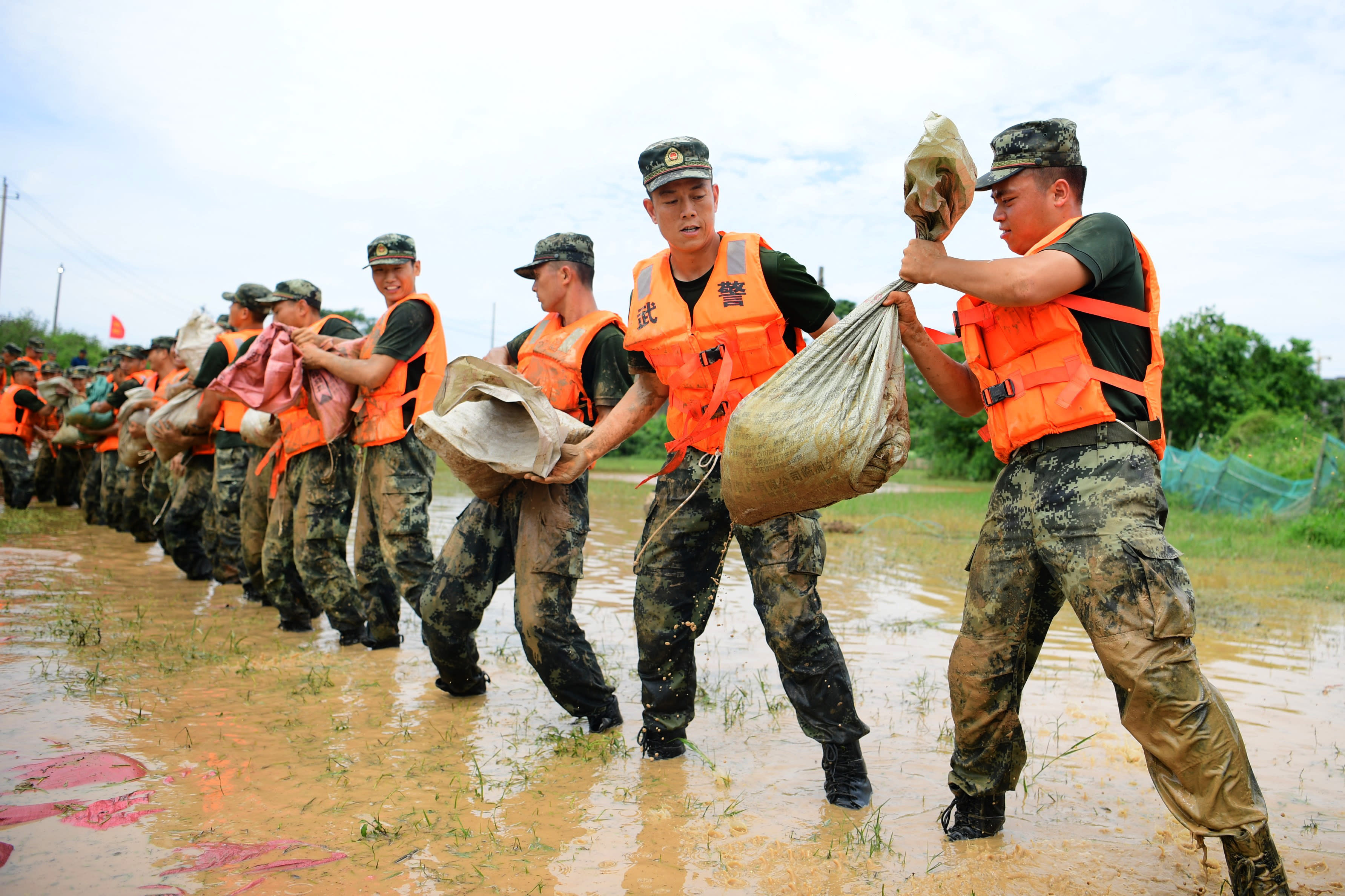 In this photo released by Xinhua News Agency, Chinese paramilitary policemen form a line to move sandbags to reinforce a dyke along the banks of Poyang Lake in Poyang County in eastern China's Jiangxi Province, Sunday, July 12, 2020. Vice Minister of Emergency Management Zheng Guoguang told reporters Monday, July 13, 2020 that the Yangtze River and parts of its watershed have seen the second highest rainfall since 1961 over the past six months. (Cao Xianxun/Xinhua via AP)