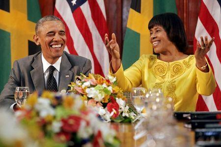 U.S. President Barack Obama (L) smiles during remarks by Jamaica's Prime Minister Portia Simpson-Miller after their meeting at Jamaica House in Kingston April 9, 2015. REUTERS/Jonathan Ernst