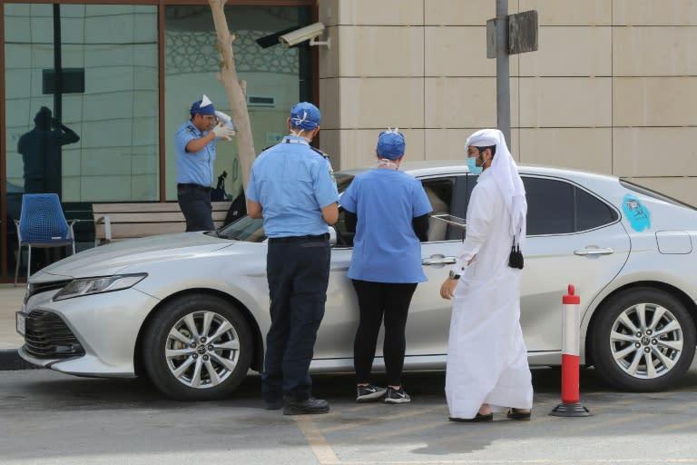 Health workers assist at a drive-thru testing service for coronavirus in the Qatari capital Doha (AFP Photo/KARIM JAAFAR)
