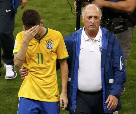 Brazil's Oscar is comforted by coach Luiz Felipe Scolari after they lost their 2014 World Cup semi-finals against Germany at the Mineirao stadium in Belo Horizonte