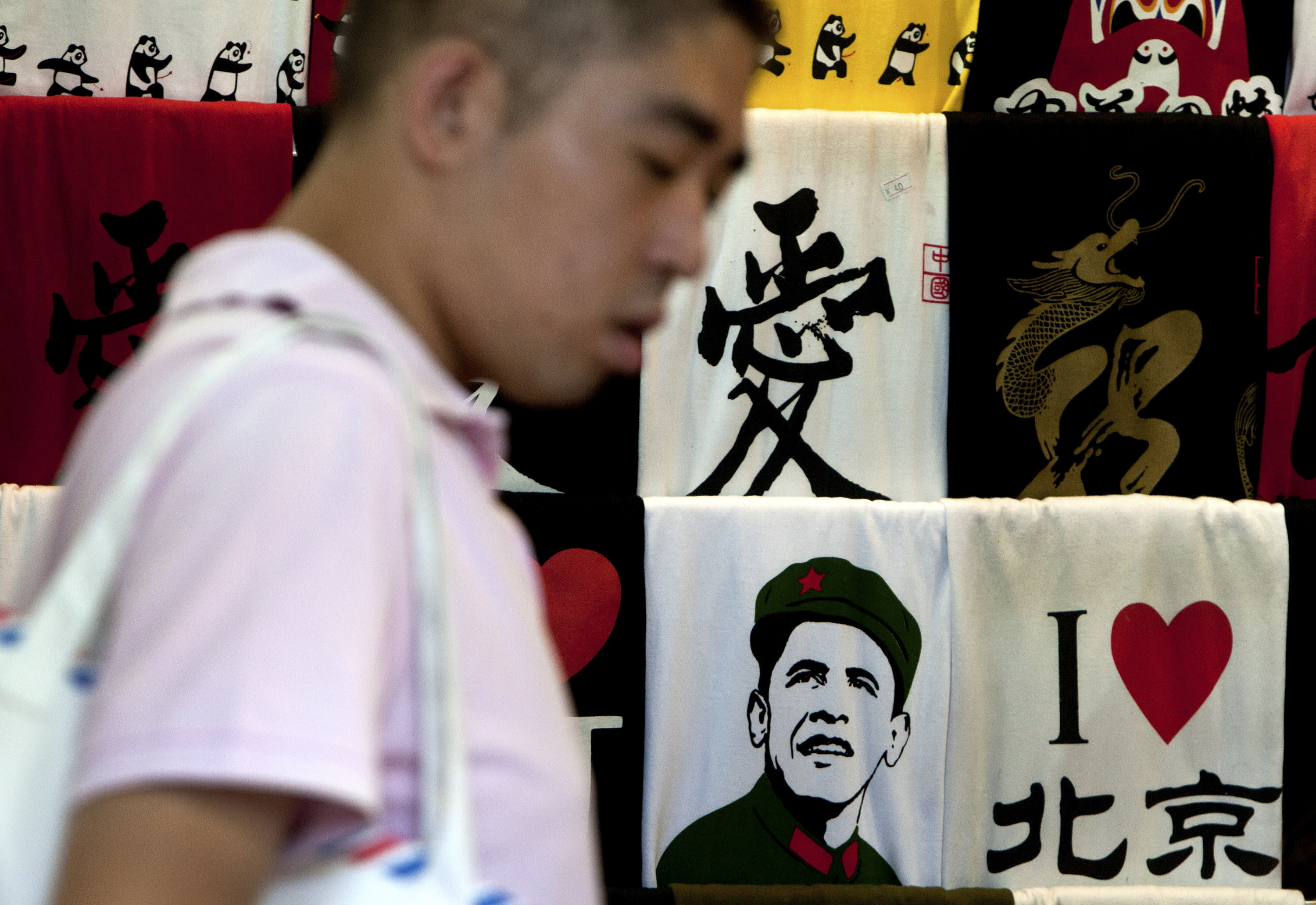 In this Sunday, July 31, 2011 photo, a Chinese man shops near a t-shirt printed with an image of U.S. President Barack Obama dressed in a Communist Cultural revolution era military uniform displayed for sale with others at a shop in Beijing, China. Obama and Chinese President Xi Jinping face weighty issues when they meet at a private estate in California next week, but their most important task may simply be establishing a strong rapport. (AP Photo/Andy Wong)